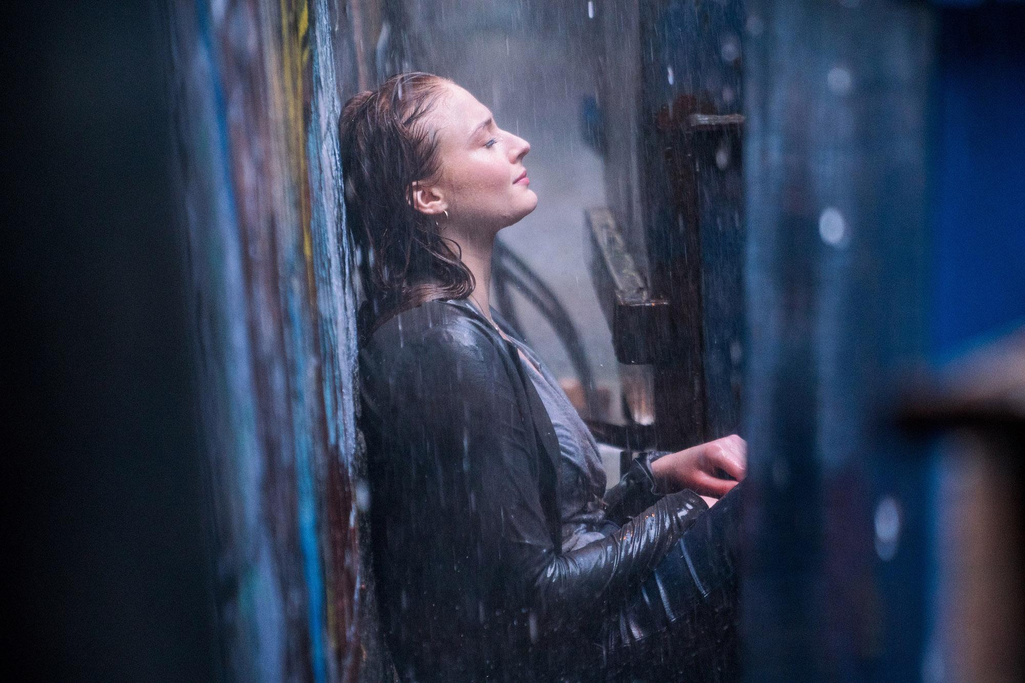 Jean Grey chora na chuva, escondida atrás de uma caçamba de lixo.