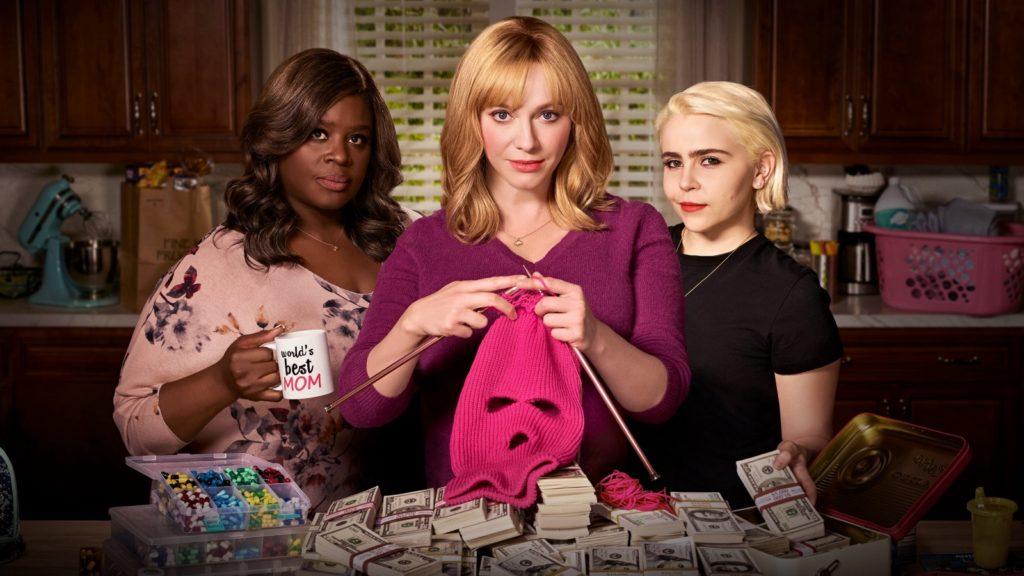 """Três mulheres posam em frente a uma pilha de dinheiro. Uma delas tricota uma máscara rosa de ladrão, enquanto outra segura uma xícara escrito """"Melhor Mãe do Mundo"""""""