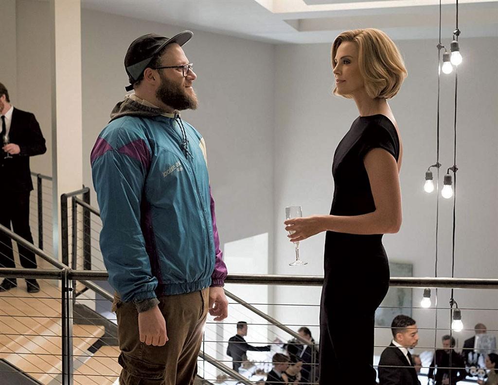 Os atores Seth Rogen e Charlize Theron em cena do filme, frente a frente em uma festa. Ele usa roupas desleixadas, enquanto ela usa roupas de gala preta.
