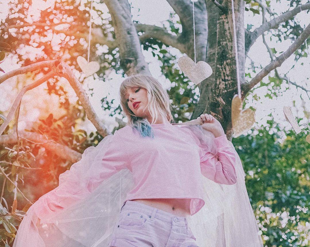Taylor Swift posa toda de rosa, em uma floresta, com diversos corações de papel pendurados.
